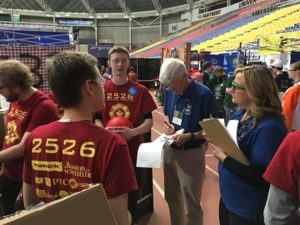 Photo of judges talking to team members at their pit.