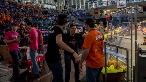 Three Alliance team members gathering in anticipation before a match.