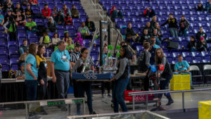 Team members moving their robot onto the field.